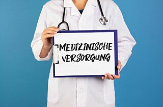 Doctor Holding Clipboard With Medizinische Versorgung Text